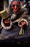 Tibet - pilgrims worshipping - elderly man with prayer wheel and beads - photo by Y.Xu