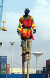 Lomé, Togo: man on stilts in the port - crane, water tower and containers in the background - Port Autonome de Lomé - photo by G.Frysinger