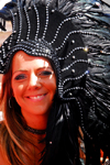 Port of Spain, Trinidad and Tobago: smiling white girl with black feathers on the head during carnival - photo by E.Petitalot