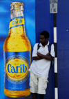 Scarborough, Tobago: man waiting for a bus in front of a drink advertising - Carib lager - photo by E.Petitalot