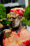 Port of Spain, Trinidad and Tobago: mud covered man drinking beer - carnival parade - Jouvert - photo by E.Petitalot