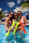 Grand Turk Island, Turks and Caicos: three young women wearing bikinis drinking tall margaritas in the pool at Jimmy Buffet's Margaritaville bar and restaurant - photo by D.Smith