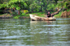 Jinja, Uganda: man on a wooden canoe - source of the Nile river, western bank - photo by M.Torres