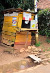 Entebbe, Wakiso District, Uganda: mobile telephone services 'shop' in the developing world, notice the 'pedestrian bridge' - wooden hut - photo by M.Torres