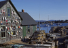 Maine, USA: lobster traps and floats on fishing wharf – wooden house with shingles - photo by C.Lovell
