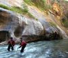 Zion National Park, Utah, USA: Virgin River Narrows - hikers with trekking poles struggle against the current - photo by B.Cain