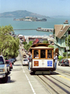 San Francisco (California): a tram climbs a hill - Alcatraz in the background - tram line nr 19 - Powel and Market - photo by M.Bergsma