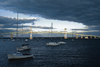 Narragansett Bay, Rhode Island, USA: boats and Claiborne Pell Newport Bridge, suspension bridge over the Atlantic Ocean - links Newport on Aquidneck Island and the Jamestown on Conanicut Island - stormy sky at sunset - photo by C.Lovell