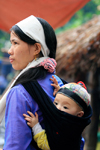 Ba Be National Park - vietnam: woman with baby - the white headscarf tells that her husband is gone recently - photo by Tran Thai