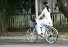 Hue - Vietnam: students have to dress the tradional long tunic - girl on a bike - photo by Tran Thai