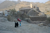Yemen - Hajja governorate - two women in black and a girl blue  near an old water reservoir - photo by E.Andersen