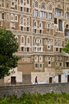 Sana'a / Sanaa, Yemen: child walking along wall in front of Old City houses - ancient skyscrapers - UNESCO World Heritage Site - houses with elaborate exterior ornamentation - photo by J.Pemberton
