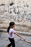 Sana'a / Sanaa, Yemen: girl in front of graffitied wall - Arabic characters - photo by J.Pemberton