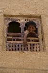 Shibam, Hadhramaut Governorate, Yemen: boy looking out window - Old Walled City of Shibam - mud building - photo by J.Pemberton