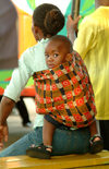 Zambia - Livingstone: waiting for a bus - curious toddler on his mother's back - photo by J.Banks
