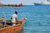 Stone Town, Zanzibar, Tanzania: a fisherman prepares his wares - boat seen from Mizingani Road - photo by M.Torres