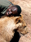 Masuwe Safari Lodge, Matabeleland North province, Zimbabwe: lion and friendly park ranger - photo by R.Eime