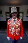 Victoria Falls - Mosi-oa-tunya, Matabeleland North province, Zimbabwe: Odwell Makamure, the famous doorman at the Victoria Falls Hotel proudly parades his collection of pins on his red coat and tall hat - photo by C.Lovell